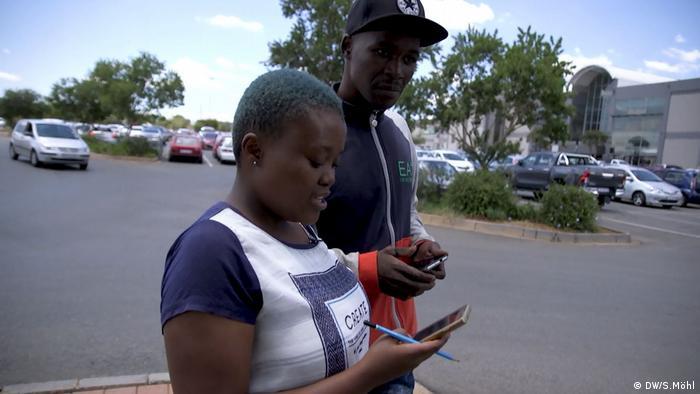 Student Mpho Mofokeng nutzt das WLAN vor einem Einkaufszentrum in Johannesburg (DW/S.Möhl)
