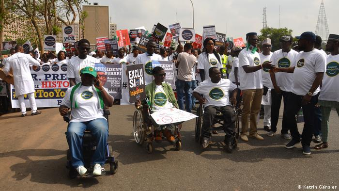 Protesters in wheel chairs and on foot carry posters