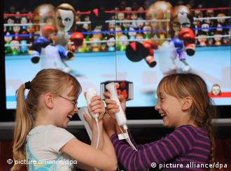 Two kids play with a Wii console