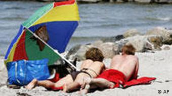 A couple lie on the beach in the shade of a large parasol