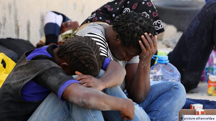 Refugees hold their heads in their hands while seated on the ground (picture-alliance/dpa)