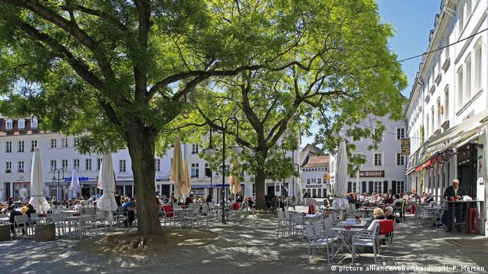 People sitting under a tree in a square