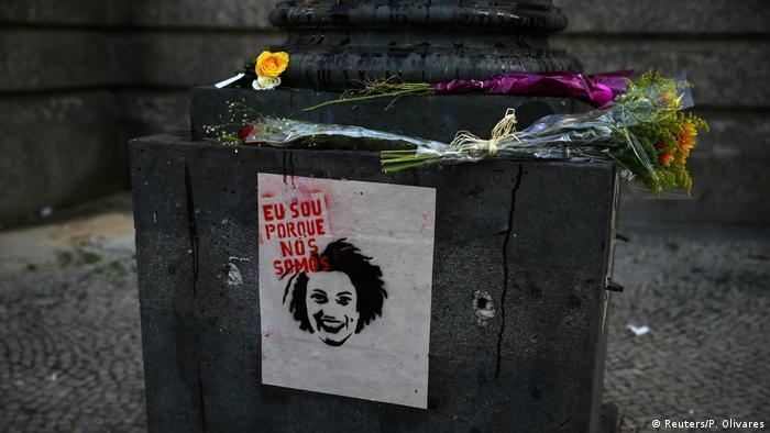 Flores e cartaz com rosto de Marielle no Rio de Janeiro: eu sou porque nós somos