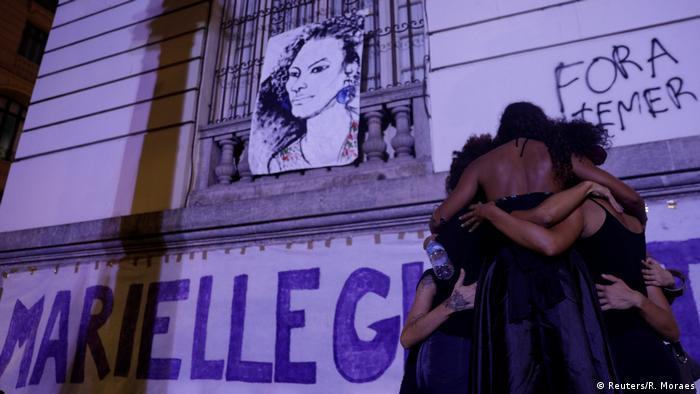Moradores se abraçam ao lado de caricatura de Marielle