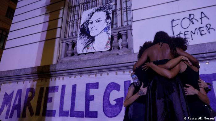 Demonstrators huddle together next to a drawing of Marielle Franco in Rio de Janeiro