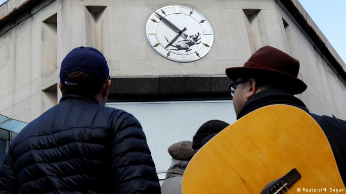 People look at Banksy's new graffiti of a rat running in a clock