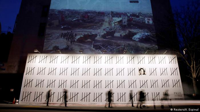 People walk in front of the banksy mural protesting Zehra Dogan's imprisonment