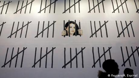 The face of Zehra Dogan looks out from behind painted black bars on a mural (Reuters/A. Espinal)