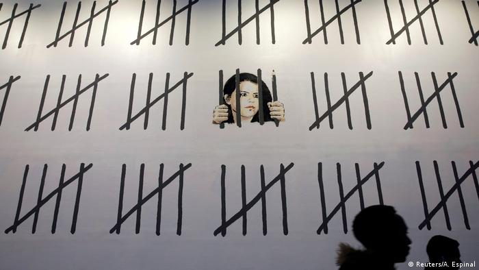 The face of Zehra Dogan looks out from behind painted black bars on a mural