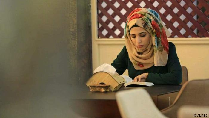 Zainab al-Jubouri, owner of the Cultural Cafe (Orama), reads her book and manages the affairs of the work (ALIABD)