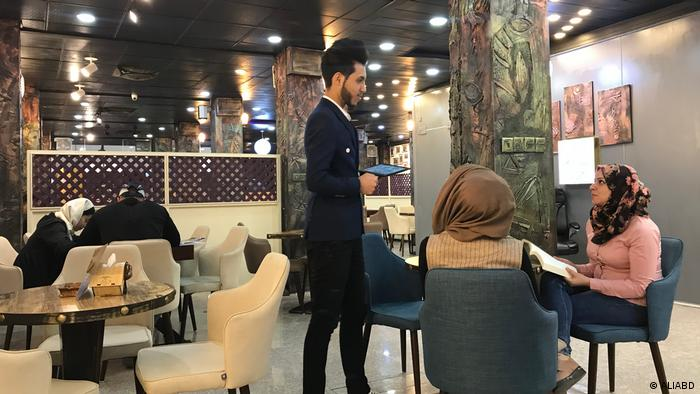 Young women from Najaf are reading books and asking for hot drinks from the coffee shop waiter (ALIABD)
