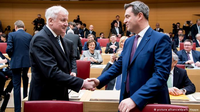 Seehofer (L) and Söder shaking hands in Bavaria's parliamentary chamber on 16 March 2018 (picture alliance/dpa/S. Hoppe)