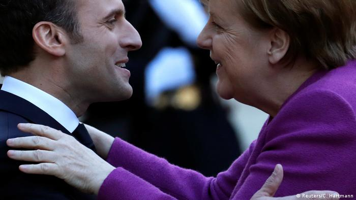 French President Emmanuel Macron welcomes German Chancellor Angela Merkel as she arrives for a meeting at the Elysee Palace in Paris (Reuters/C. Hartmann)