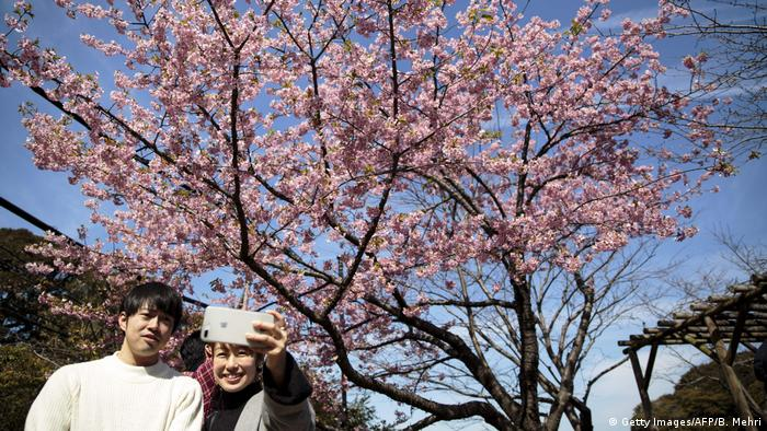 Couple taking selfie in front of cherry tree