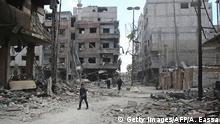 Syrians walk along a destroyed street in eastern Ghouta, Syria
