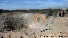A crater marks the spot where an Israeli missile struck an underground military site in Gaza