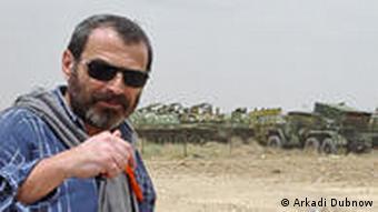 Аркадий Дубнов на фоне кладбища советской военной техники в Кандагаре