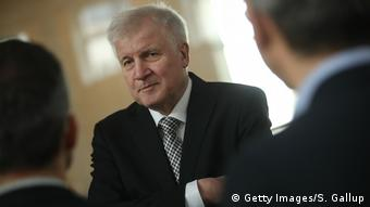 German Interior Minister designate and Bavarian Christian Democrat (CSU) Horst Seehofer chats with journalists during a break in the swearing-in of the new German government at the Bundestag on March 14, 2018 in Berlin, Germany