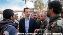 Syrian President Bashar Assad is surrounded by Syrian soldiers during his visit to eastern Ghouta area