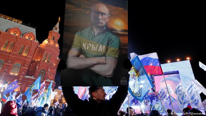 A man holding up a placard showing a painting of Putin wearing a shirt with Crimea written on it in Russian (Reuters/M. Shemetov)