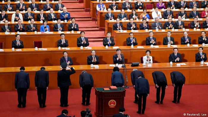 Newly elected vice premiers and state councillors make a bow to Chinese President Xi Jinping