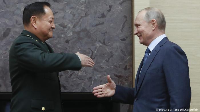 Der russische Präsident Wladimir Putin schüttelt dem stellvertretenden Vorsitzenden der Zentralen Militärkommission Zhang Youxia die Hand (picture-alliance/S.Karpukhin)