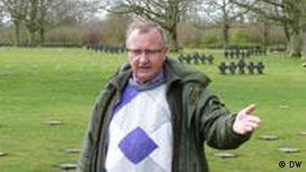 Lucien Tisserand pointing to a row of stone crosses