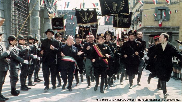 Italy film still from Amarcord shows men marching down a street (picture-alliance/Mary Evans Picture Library/Ronald Grant Archive)