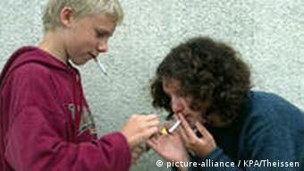 214436.jpg Junge und Maedchen rauchen heimlich / MR young girl and boy lightening secretly a cigarette ||rights=RM