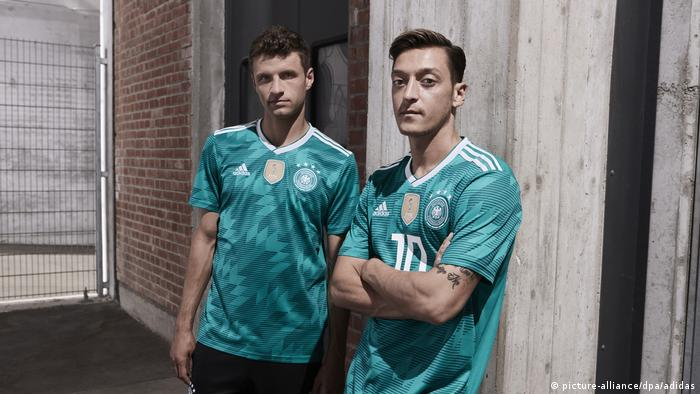 Thomas Müller und Mesut Özil, football players on Germany's national team, stand next to each other