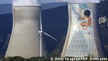 A picture taken on April 7, 2011 shows windmills and a painting on the Cruas Meysse nuclear power plant located in Cruas and Meysse communes, next to the Rhone River. The site is 35km north of Tricastin Nuclear Power Center and near the town of Montélimar. The site contains 4 pressurized water reactors of 900 MW each, totaling 3600 MW total. The construction began in 1978, the reactors were built between 1983 and 1984.AFP PHOTO/PHILIPPE DESMAZES (Photo credit should read PHILIPPE DESMAZES/AFP/Getty Images)