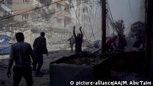 DAMASCUS, SYRIA - MARCH 20 : People run through the damaged buildings after Assad Regime forces carried out airstrikes in Eastern Ghouta's Douma town in Damascus, Syria on March 20, 2018. At least 59 civilians were killed by the Assad regime and its supporters in the besieged Eastern Ghouta region on Tuesday, Syrian Civil Defense sources said. Mouneb Abu Taim / Anadolu Agency   Keine Weitergabe an Wiederverkäufer.