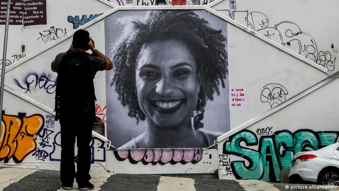 A massive photo of Marielle Franco hangs on the wall of a staircase on the street in Sao Paulo