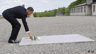 اوباما در حال گذاشتن شاخهای رز سپید بر لوح یادبود قربانیان در محل ورودی اردوگاه بوخنوالد