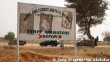 Soldiers (R) drive past a signpost leading to the Government Girls Science and Technical College staff quarters in Dapchi