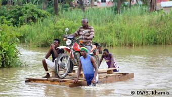 People guiding a motobike on a raft acorss the water (DW/S. Khamis)