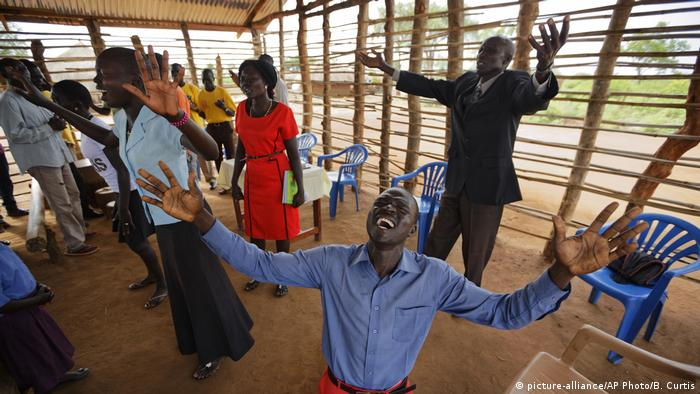 Pentecostalists in South Sudan, raising their arms up in prayer.