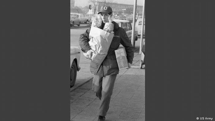 Man with a shopping bag in the photo exhibition Little America (US Army ).