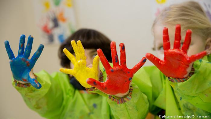 Kids showing their brightly-colored hands (picture-alliance/dpa/D. Karmann)