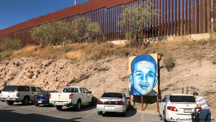 A large, mounted, painting of Jose Antonio Elena Rodriguez stands at the base of the embankment on the Mexican side of the US-Mexican border.