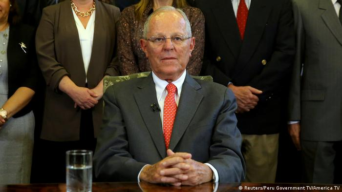 Peruvian President Pedro Pablo Kuczynski sits at table with hands folded as he announces resignation in TV address to the nation.