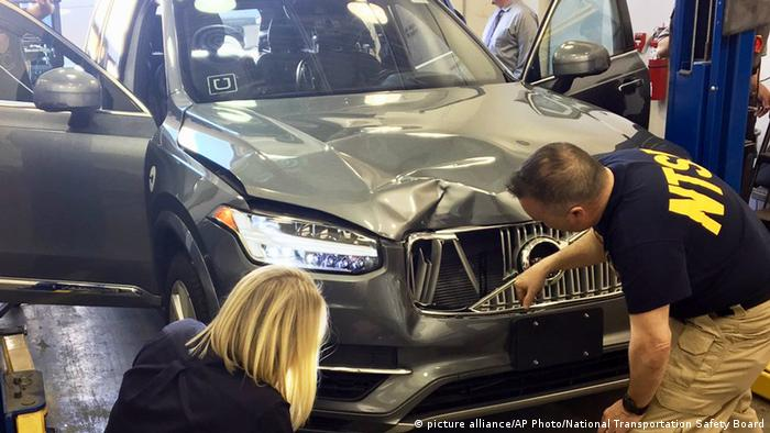 investigators examine a driverless Uber SUV that fatally struck a woman in Tempe, Ariz