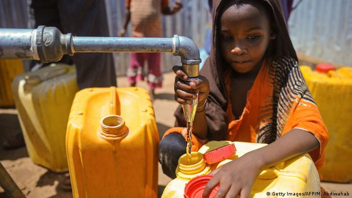 A child in Somalia collects water from a well