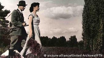 Ein Jäger und eine Frau spazieren über eine Blumenwiese
