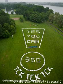 Climate activists in Bonn line up in an exclamation point reading Yes you can and tick, tick, tick