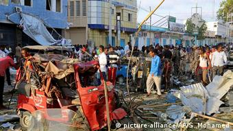 people milling around street, destroyed vehicle, after explosion (picture-alliance/AA/S. Mohamed)