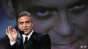 George Clooney vor Clooney-Bild (Foto: AP Photo/Domenico Stinellis)