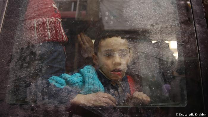A boy looks through a bus window during an evacuation from the besieged town of Douma, Eastern Ghouta near Damascus, Syria. (REUTERS/Bassam Khabieh)