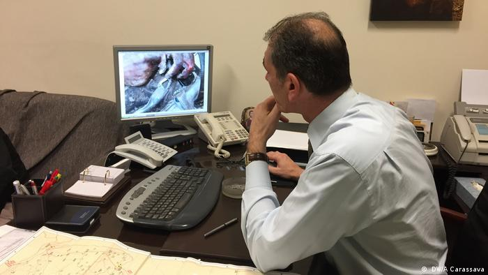 Coroner Pavlos Pavlidis looks at an image of a person found trying to cross the Greek border to get to the EU