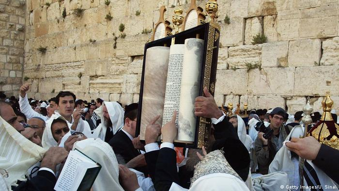 Religious Jews cover themselves with prayer shawls as they perform the priestly blessing during Passover festivities at the Western Wall